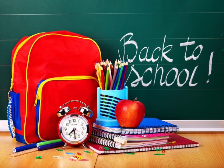 Back to school supplies with backpack in front of chalkboard