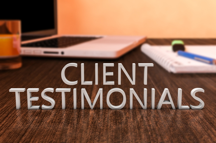 Client Testimonials - letters on wooden desk with laptop computer and a notebook.
