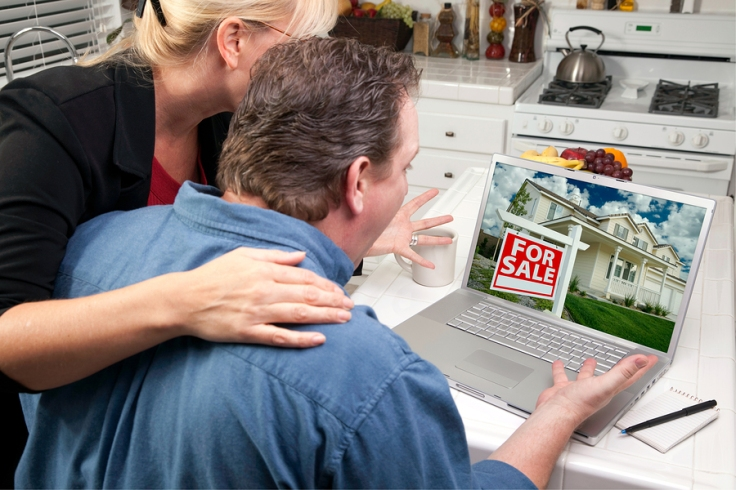 Couple in kitchen using a laptop to search internet for homes for sale