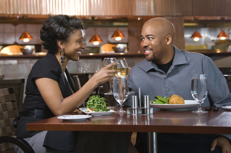 African-American couple dining out. They are toasting with glasses of wine and smiling