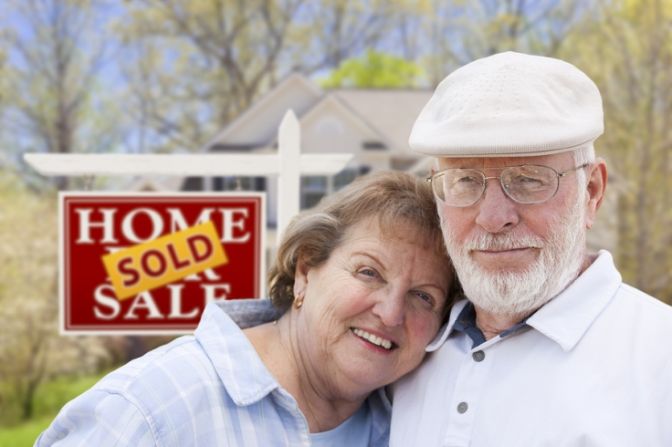 Smiling senior couple in front of a house sold sign
