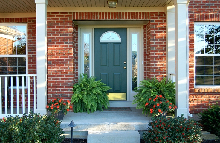 Attractive home entrance with covered porch, potted plants, and green door with sidelights